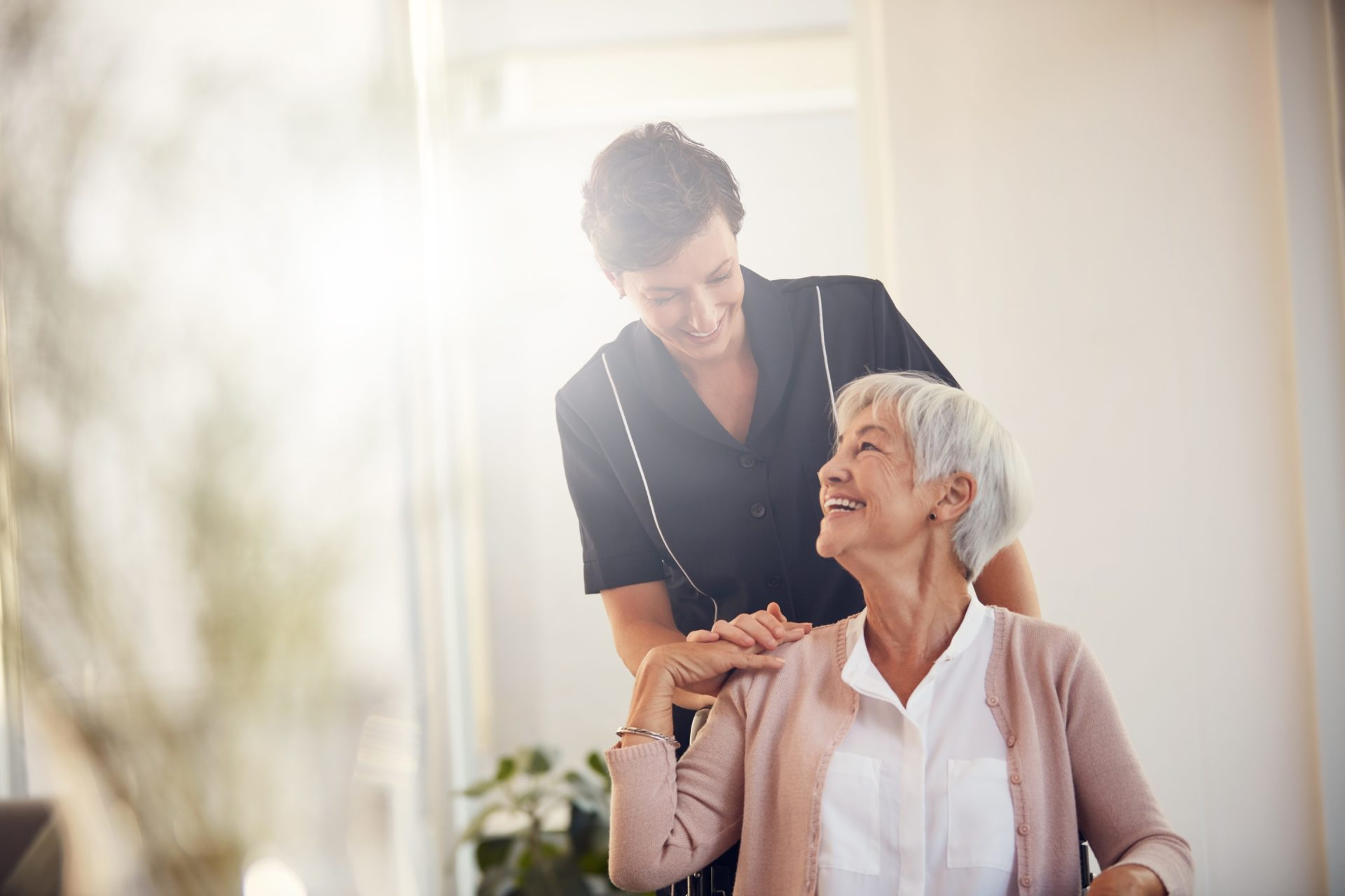 Cropped shot of a young female nurse caring for a senior woman sitting in a wheelchair in a nursing home